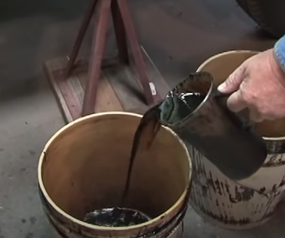 Pouring captured bio oil into bucket.